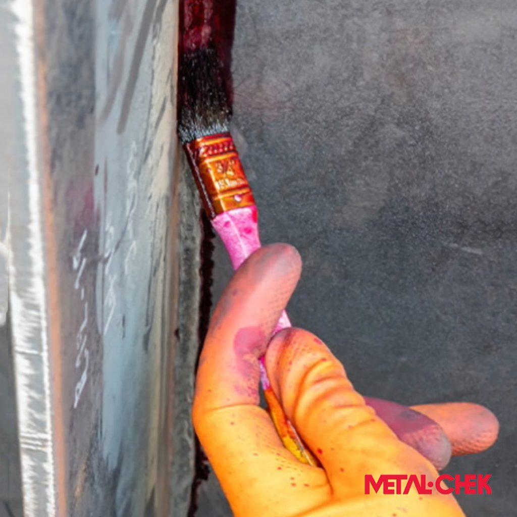 Detalhe de aplicação de líquido penetrante por pincel.
